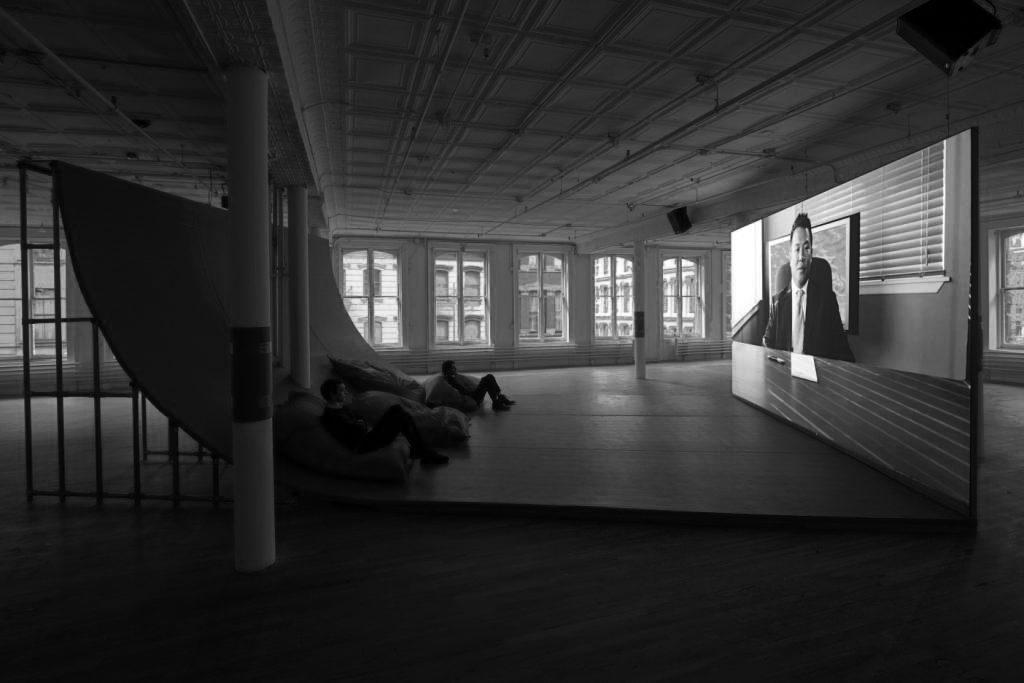 展览现场:黑特•史德耶尔,《博物馆是战场吗?》,有声双频高清录像,40分钟, 2013,承蒙艺術家惠允使用。Hito Steyerl, Is a Museum a Battlefield? (2013), Dual-channel, High-resolution video with audio. 40 minutes. Courtesy of the artist.