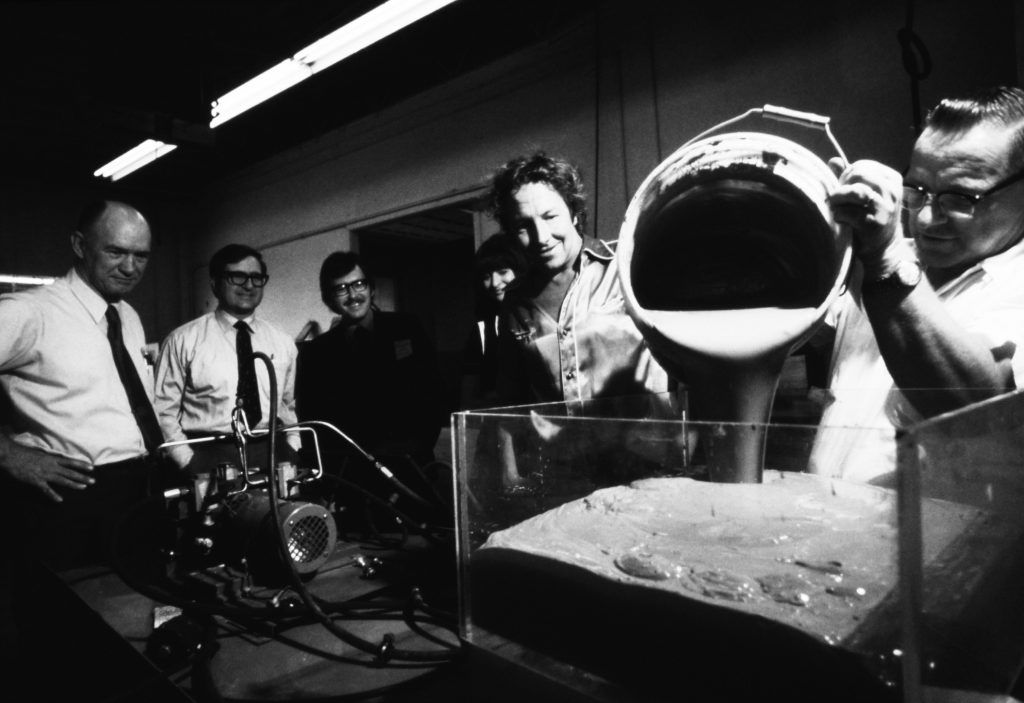 "Robert Rauschenberg( second from right ), engineers from Teledyne, and LACMA curators Maurice Tuchman and Gail Scott( third and fourth from left ) viewing a prototype model for Rauschenberg's Art and Technology piece Mud Muse, 1970. ©2015 Robert Rauschenberg Foundation/Licensed by VAGA, New York, NY. Photo ©Malcolm Lubliner 罗伯特·劳森伯格( 右二 )、来自特利丹的工程师以及洛杉矶郡立美术馆两位策展人莫里斯·图赫曼( 左三 )和盖尔·斯科特( 左四 )正在观看罗伯特·劳森伯格的""艺术与科技""作品的原型:Mud Muse,1970。照片来源:罗伯特·劳森伯格基金会"